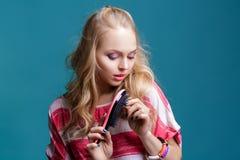 Junge attraktive blonde Frau, die ihr Haar mit rosa Kamm auf blauem Hintergrund bürstet Stockbild