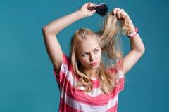 Junge attraktive blonde Frau, die ihr Haar mit rosa Kamm auf blauem Hintergrund bürstet Lizenzfreies Stockbild