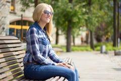 Junge attraktive blonde Frau, die im Park sitzt Lizenzfreie Stockbilder
