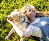 Junge attraktive blonde Frau, die mit ihrem Hund im grünen Park am Sommer, Lebensstilleutekonzept spielt Stockbild