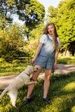 Junge attraktive blonde Frau, die mit ihrem Hund im grünen Park am Sommer, Lebensstilleutekonzept spielt Stockbilder