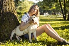 Junge attraktive blonde Frau, die mit ihrem Hund im grünen Park am Sommer, Lebensstilleutekonzept spielt Stockfoto