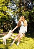 Junge attraktive blonde Frau, die mit ihrem Hund im grünen Park am Sommer, Lebensstilleutekonzept spielt Lizenzfreie Stockfotos