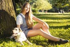 Junge attraktive blonde Frau, die mit ihrem Hund im grünen Park am Sommer, Lebensstilleutekonzept spielt Stockfotografie