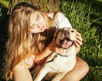 Junge attraktive blonde Frau, die mit ihrem Hund im grünen Park am Sommer, Lebensstilleutekonzept spielt Lizenzfreies Stockfoto
