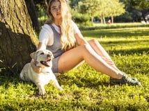 Junge attraktive blonde Frau, die mit ihrem Hund im grünen Park am Sommer, Lebensstilleutekonzept spielt Lizenzfreie Stockfotografie