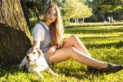 Junge attraktive blonde Frau, die mit ihrem Hund im grünen Park am Sommer, Lebensstilleutekonzept spielt Lizenzfreie Stockbilder