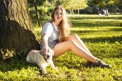 Junge attraktive blonde Frau, die mit ihrem Hund im grünen Park am Sommer, Lebensstilleutekonzept spielt Lizenzfreies Stockbild