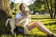 Junge attraktive blonde Frau, die mit ihrem Hund im grünen Park am Sommer, Lebensstilleutekonzept spielt Stockfotos
