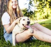 Junge attraktive blonde Frau, die mit ihrem Hund im grünen Park spielt Lizenzfreies Stockfoto