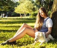 Junge attraktive blonde Frau, die mit ihrem Hund im grünen Park spielt Lizenzfreie Stockbilder