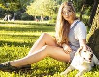 Junge attraktive blonde Frau, die mit ihrem Hund im grünen Park spielt Lizenzfreies Stockbild