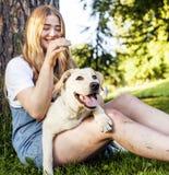 Junge attraktive blonde Frau, die mit ihrem Hund im grünen Park spielt Lizenzfreie Stockfotos