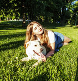 Junge attraktive blonde Frau, die mit ihrem Hund im grünen Park spielt Stockbilder