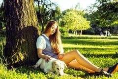 Junge attraktive blonde Frau, die mit ihrem Hund im grünen Park spielt Lizenzfreie Stockfotografie