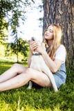 Junge attraktive blonde Frau, die mit ihrem Hund im grünen Park spielt Stockbild