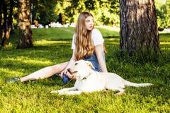 Junge attraktive blonde Frau, die mit ihrem Hund im grünen Park spielt Stockfoto