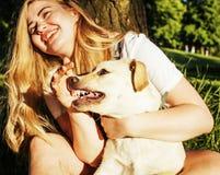 Junge attraktive blonde Frau, die mit ihrem Hund im grünen Park spielt Stockfotos