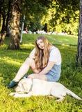 Junge attraktive blonde Frau, die mit ihrem Hund im grünen Park spielt Stockfotografie