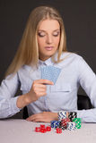 Junge attraktive blonde Frau, die Poker über Grau spielt Stockbild