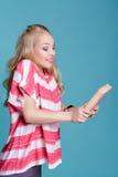 Junge attraktive blonde Frau, die rosa Buch auf blauem Hintergrund hält Stockfotos