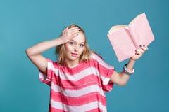 Junge attraktive blonde Frau, die rosa Buch auf blauem Hintergrund hält Stockfotografie