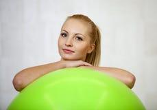 Junge attraktive blonde Frau, die von hinten einen Eignungsball lächelt Lizenzfreies Stockfoto