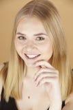 Junge attraktive blonde Frau mit dem Finger an ihrem Gesicht Lizenzfreies Stockfoto