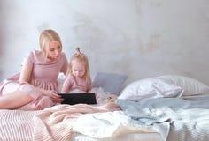 Junge attraktive blonde Frau mit ihrer kleinen reizend Tochter im Rosa kleidet das Aufpassen etwas in der Tablette und die Unterh Stockfoto
