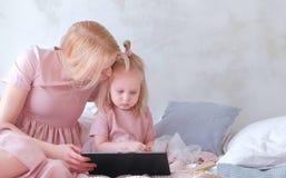 Junge attraktive blonde Frau mit ihrer kleinen reizend Tochter im Rosa kleidet etwas in der Tablette seriosly aufpassen Stockbilder