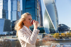 Junge attraktive blonde Frau in trinkendem Kaffee der beige Jacke draußen Lizenzfreie Stockfotografie