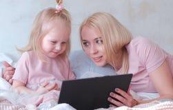 Junge attraktive blonde Frau unterrichtet ihre kleine reizend Tochter in den rosa Kleidern unter Verwendung einer Tablette, die a Stockbilder