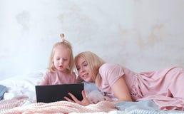 Junge attraktive blonde Frau unterrichtet ihre kleine reizend Tochter in den rosa Kleidern unter Verwendung einer Tablette, die a Lizenzfreies Stockbild