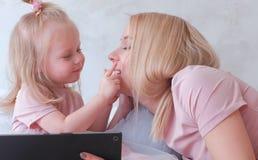 Junge attraktive blonde Frau unterrichtet ihre kleine reizend Tochter in den rosa Kleidern unter Verwendung einer Tablette, die a Stockbild