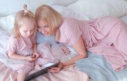 Junge attraktive blonde Frau unterrichtet ihre kleine reizend Tochter in den rosa Kleidern unter Verwendung einer Tablette, die a Stockfoto