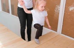 Junge attraktive blonde Mutter hinunter die Schritte mit ihrer reizend Tochter Lizenzfreies Stockfoto