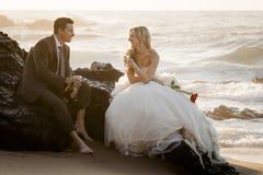 Junge attraktive Brautpaare auf Strand mit Wein stockfoto