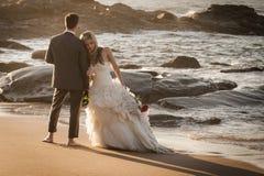 Junge attraktive Brautpaare auf Strand mit Wein Stockfotografie