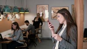 Junge attraktive Brunettegeschäftsfrau benutzt eine Tablette des Bildschirm- im modernen Startbüro Lizenzfreies Stockfoto
