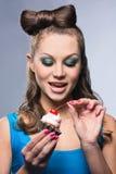 Junge attraktive Dame, die einen Kuchen isst Lizenzfreies Stockbild