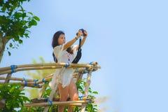 Junge attraktive Fotograffrau, die selfie Fotoporträt mit Spiegelreflexkamera der schönen Landschaft mit Baumvegetation a nimmt Lizenzfreie Stockfotos