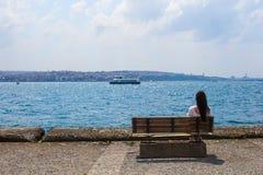 Junge attraktive Frau auf der Bank während des Sommers Lizenzfreie Stockfotografie