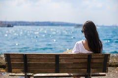Junge attraktive Frau auf der Bank während des Sommers Lizenzfreies Stockbild