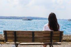 Junge attraktive Frau auf der Bank während des Sommers Stockfoto