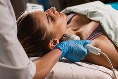 Junge attraktive Frau bei Empfang im Kosmetiker ` s Büro Verfahren elektrisches myostimulation Hardware Cosmetology Stockbilder