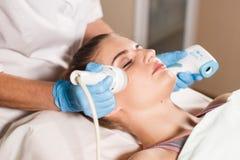 Junge attraktive Frau bei Empfang im Kosmetiker ` s Büro Verfahren elektrisches myostimulation Hardware Cosmetology Lizenzfreie Stockbilder