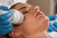 Junge attraktive Frau bei Empfang im Kosmetiker ` s Büro Verfahren elektrisches myostimulation Hardware Cosmetology Lizenzfreies Stockfoto