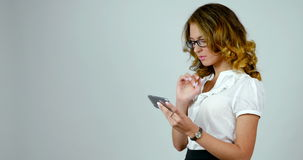 Junge attraktive Frau benutzt Smartphone, Gesamtlänge vom Studio, die Geschäftsfrau, die auf weißem Hintergrund lokalisiert wird stock footage