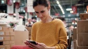 Junge attraktive Frau in der orange Jacke benutzt einen Smartphone und sitzt unter den Sachen in einem Speicher Stockfotografie