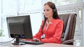 Junge attraktive Frau in der roten Jacke, die auf Schreibtisch am Kopf der Exekutive in der roten Jacke sitzt Hält Videokonferenz stock footage